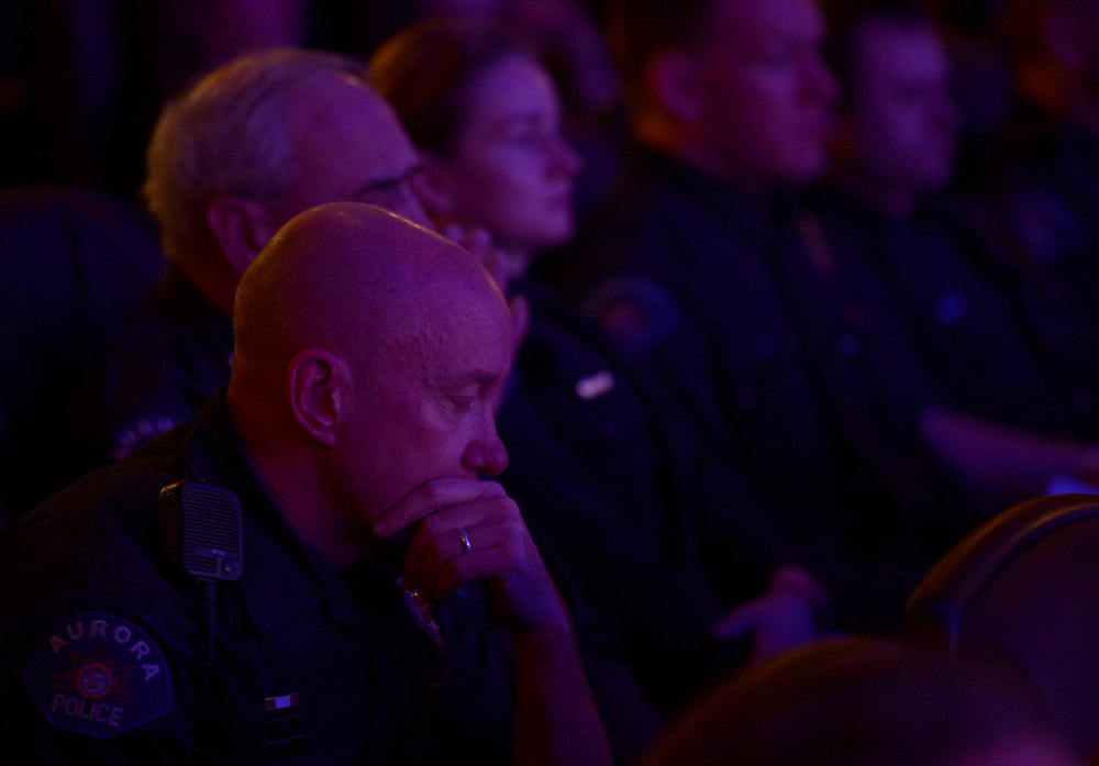 Description of . AURORA, CO. - JANUARY 17:  Aurora Police Officer Mike Hawkins, a 18 year veteran and first responder to the shooting sits with other Aurora Police officers during the reopening and remembrance in Theater I XD  of the Century Aurora Theater. James Holmes is accused of killing 12 people and wounding 70 others on July 20, 2012 in theater 9. (Photo By RJ Sangosti / The Denver Post)