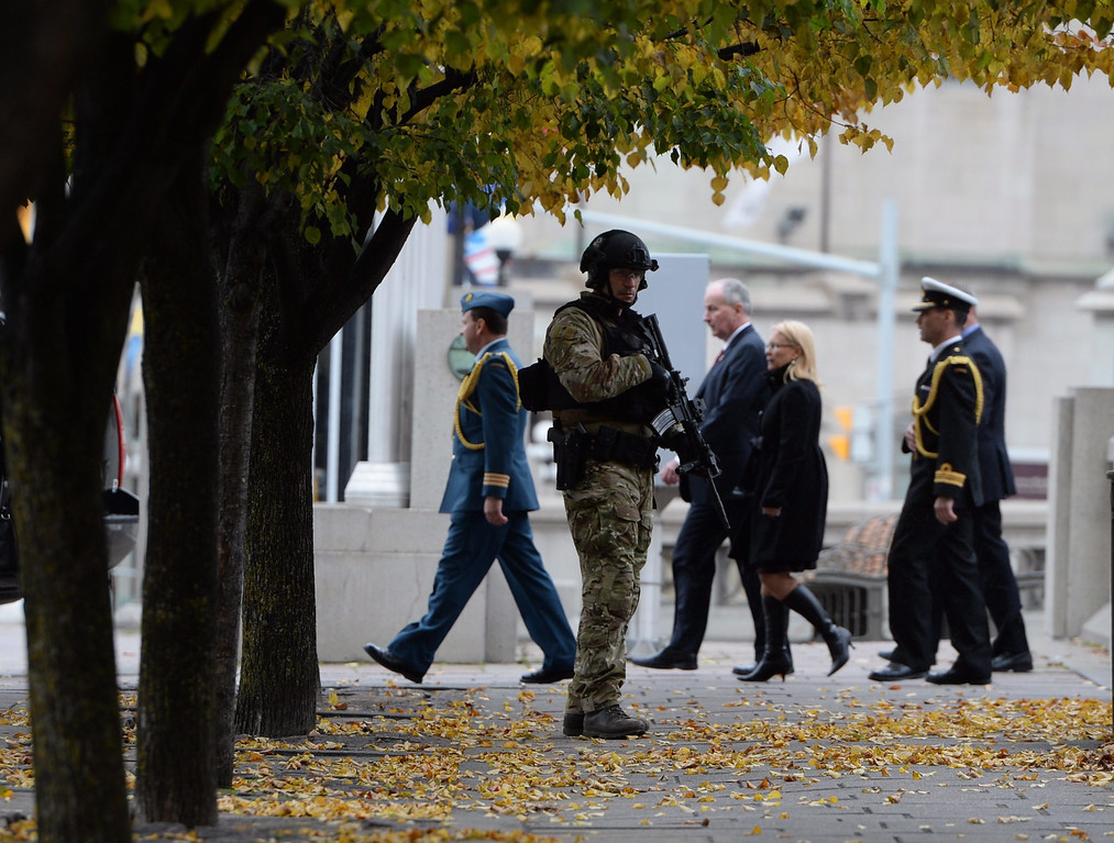 . RCMP patrol at the National War Memorial as the Minister of Defense Rob Nicholson walks past in Ottawa on Thursday, Oct. 23, 2014.    (AP Photo/The Canadian Press, Sean Kilpatrick)