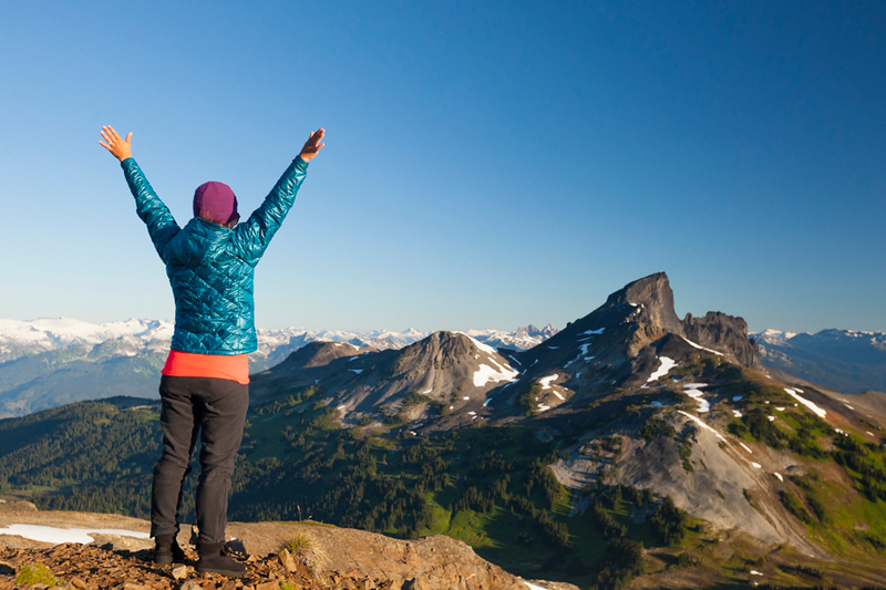 A young woman celebrates after reaching the summit of Panorama Ridge in Garibaldi Provincial Park, British Columbia, Canada.