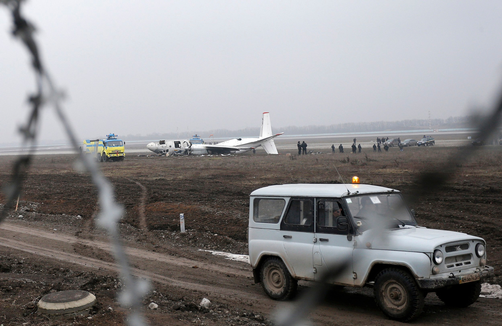Description of . A view shows the damaged twin-engined Antonov turboprop plane, which broke up during an emergency landing the day before, near the landing strip of the airport in Donetsk, February 14, 2013. At least five people were killed when a plane carrying supporters to a European soccer match in eastern Ukraine overshot the runway and broke up when it attempted an emergency landing late on Wednesday, officials said. The twin-engined Antonov turboprop was bringing 45 passengers and crew on a charter flight from the Black Sea coastal city of Odessa to Donetsk - most of them fans looking forward to attending a Champions League clash between the Ukrainian home team Shakhtar and Germany's Borussia Dortmund. REUTERS/Valeriy Bilokryl