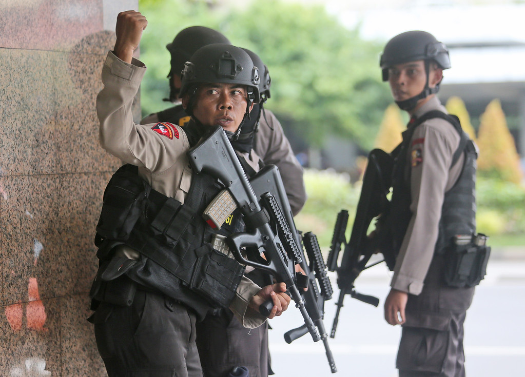 . A police officer gives a hand signal to a squad mate as they search a building near the site of an explosion in Jakarta, Indonesia Thursday, Jan. 14, 2016.  Attackers set off explosions at a Starbucks cafe in a bustling shopping area of downtown Jakarta and waged gun-battles with police Thursday, leaving bodies in the streets as office workers watched in terror from high-rise windows. (AP Photo/Tatan Syuflana)