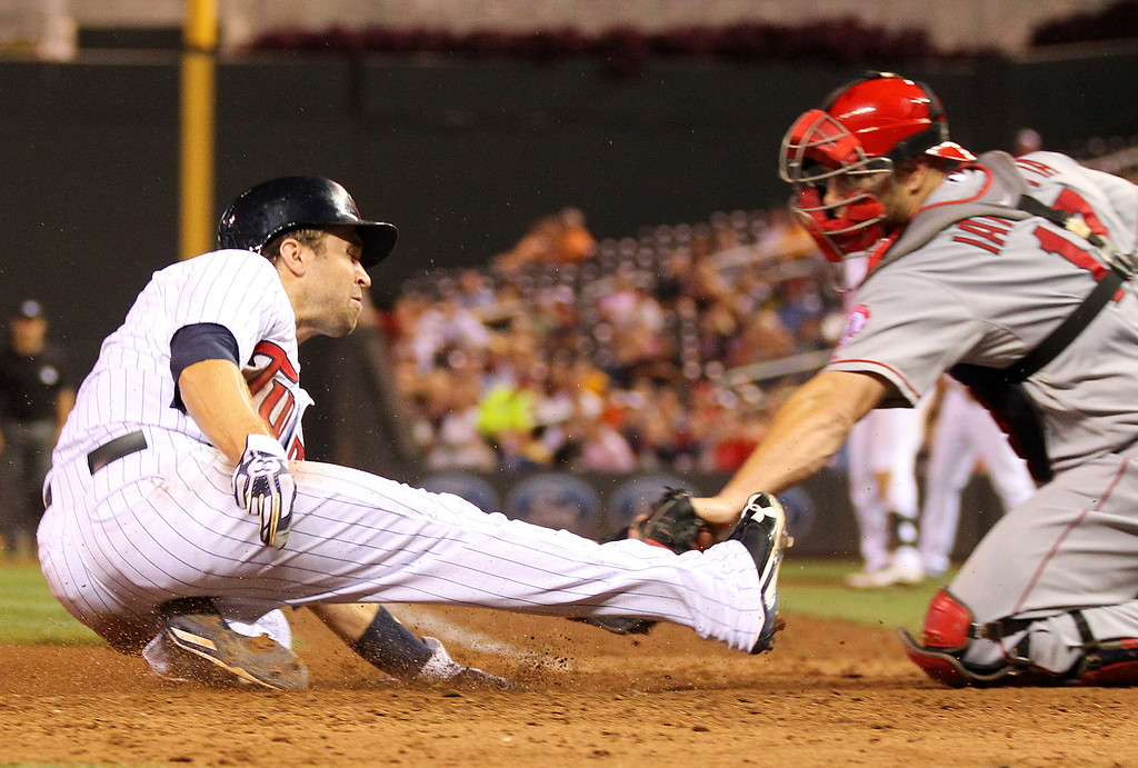 . Minnesota Twins Brian Dozier, left, slides safely into home base with Los Angeles Angels catcher Chris Iannetta late on the tag in the seventh inning of their baseball game in Minneapolis Monday, Sept. 9, 2013.(AP Photo/Andy Clayton-King)