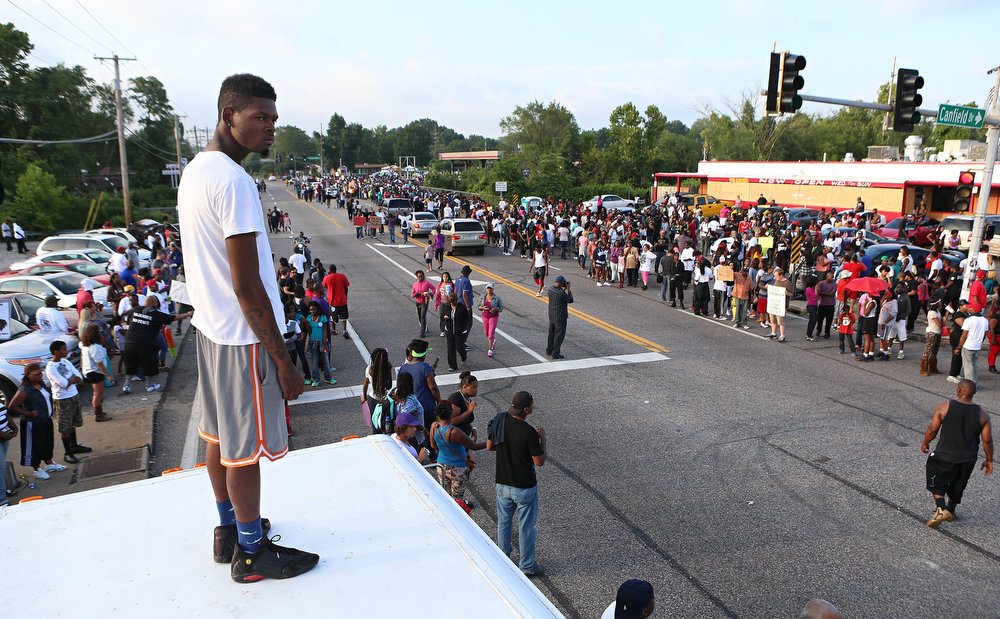 . Jamel Easley, from the Walnut Park neighborhood in St. Louis, Mo., stands on top of a van parked at the corner of Canfield Drive and West Florissant Avenue to look at protesters in Ferguson, Mo. on Sunday, Aug. 17, 2014. On Saturday, Aug. 9, 2014, a white police officer fatally shot Michael Brown, an unarmed black teenager, in the St. Louis suburb. (AP Photo/St. Louis Post-Dispatch, David Carson)