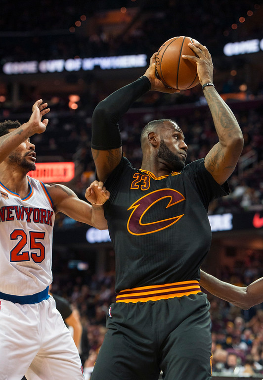 . Cleveland Cavaliers\' LeBron James (23) grabs a rebound in front of New York Knicks\' Derrick Rose (25) during the second half of an NBA basketball game in Cleveland, Tuesday, Oct. 25, 2016. (AP Photo/Phil Long)