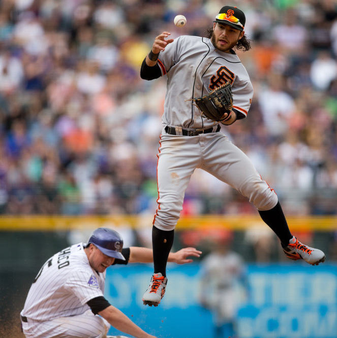 . Shortstop Brandon Crawford #35 of the San Francisco Giants bobbles the exchange while jumping over Jordan Pacheco #15 of the Colorado Rockies allowing the runner at first base to be safe during the fifth inning at Coors Field on May 19, 2013 in Denver, Colorado. The Rockies defeated the Giants 5-0. (Photo by Justin Edmonds/Getty Images)