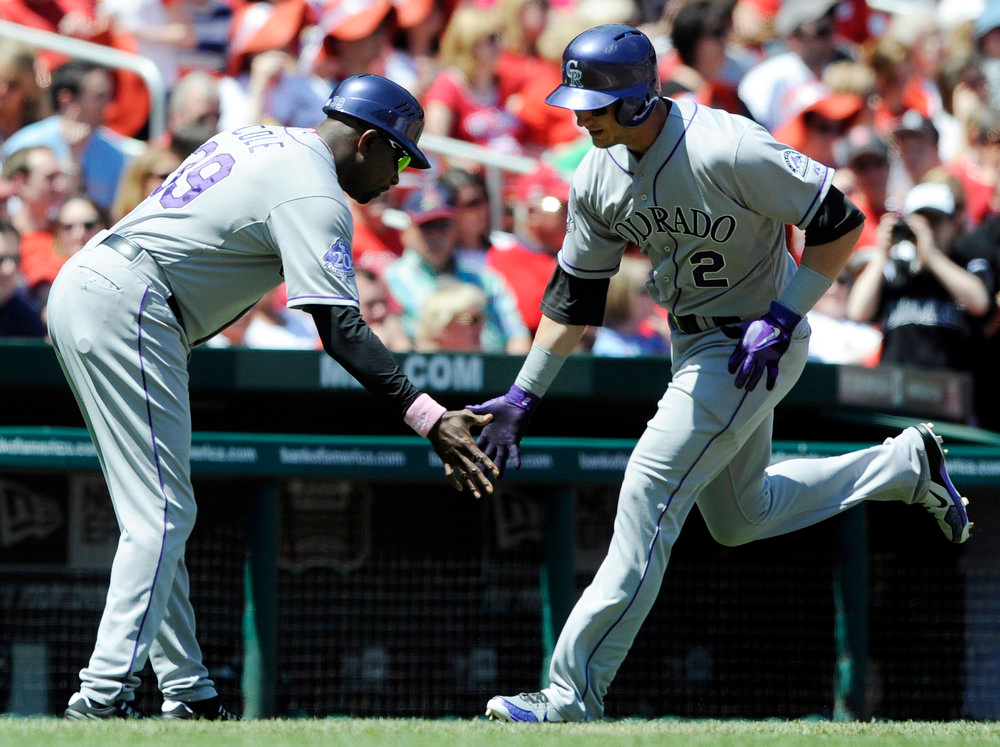 . Colorado Rockies\' Troy Tulowitzki (2) is congratulated by third base coach Stu Cole (39) after hitting a three-run home run against the St. Louis Cardinals in the third inning in a baseball game on Sunday, May 12, 2013, at Busch Stadium in St. Louis. (AP Photo/Bill Boyce)