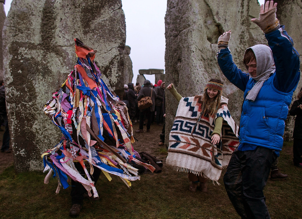 . People dance as a man dressed in a rag costume plays an accordion, as druids, pagans and revellers gather, hoping to see the sun rise as they take part in a winter solstice ceremony at Stonehenge on December 21, 2013 in Wiltshire, England.  (Photo by Matt Cardy/Getty Images)