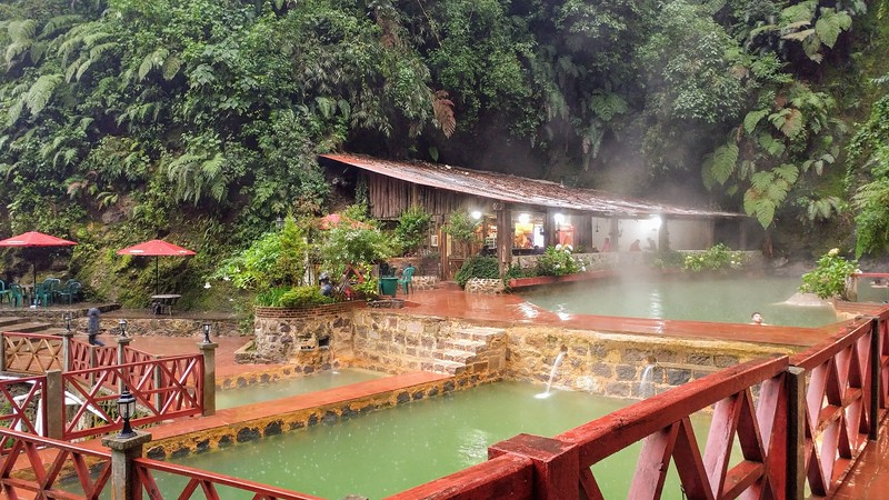hot springs surrounded by walking paths and a cafe in the background