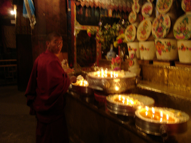 monk collecting candle butter offerings in a temple