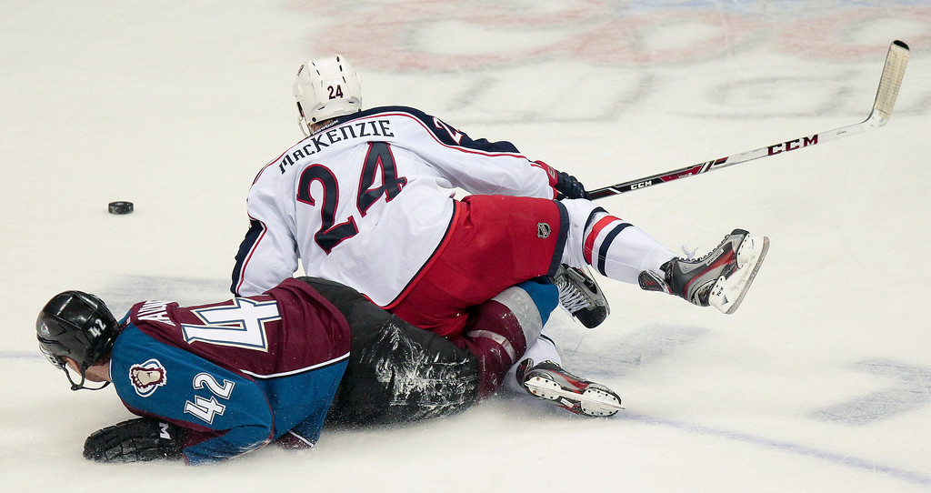 . Colorado Avalanche\'s Brad Malone (42) and Columbus Blue Jackets\' Derek MacKenzie (24) slide across the ice after colliding during the first period of an NHL hockey game on Monday, April 15, 2013 in Denver. (AP Photo/Barry Gutierrez)