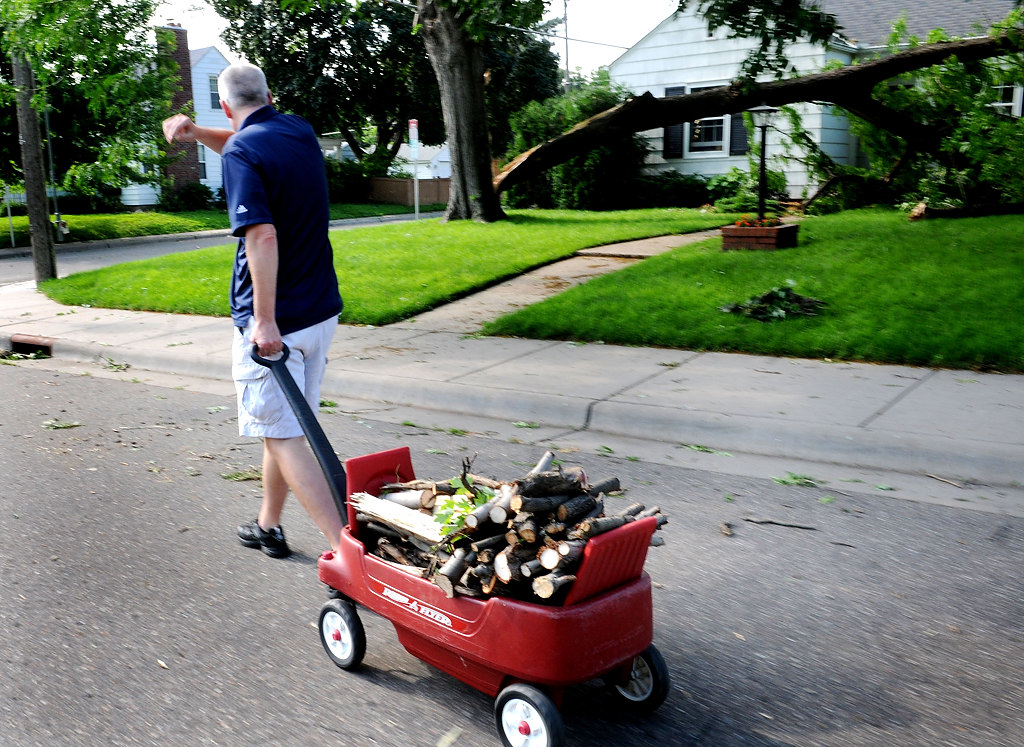 . Dave Elmstrom of St. Paul lent his neighbor his chain saw and was able to take wood back to his home Saturday afternoon in Highland Park. (Pioneer Press: Sherri LaRose-Chiglo)