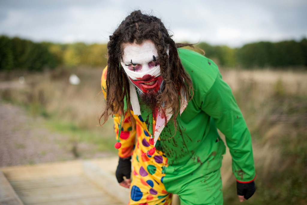 """. A zombie clown prepares for the runners as he takes part in one of Britain\'s biggest horror events, the \""""Zombie Evacuation Race\"""" at Carver Barracks near Saffron Walden, England, on October 5, 2013. The race sees thousands of participants attempt to complete a gruelling 5 kilometre cross-country run, while evading \""""zombies\"""", intent on snatching the three life-line strips hanging from every runner\'s waist.  Those who manage to get through with any strips remaining are named as survivors while those without take home an \""""infected\"""" badge.  LEON NEAL/AFP/Getty Images"""