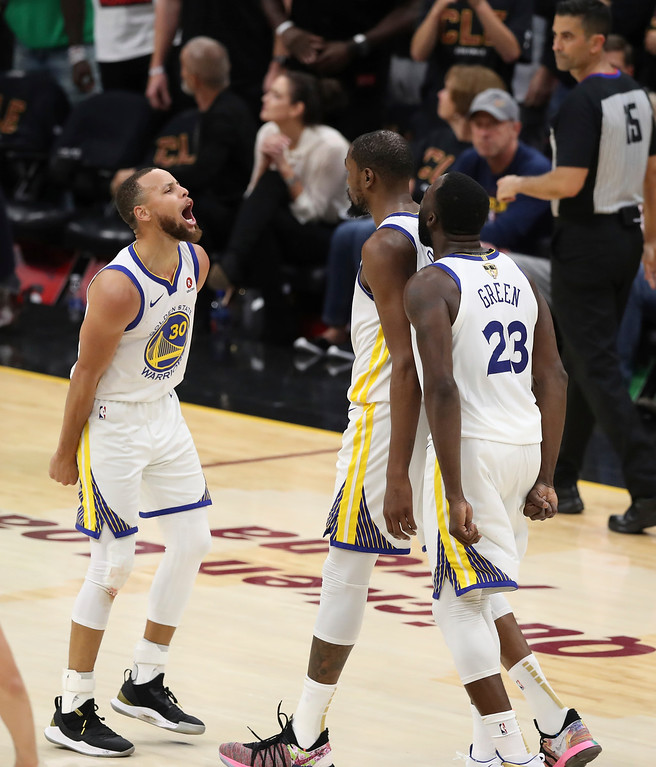 . Golden State Warriors\' Kevin Durant celebrates with Stephen Curry, left, and Draymond Green (23) in the second half of Game 3 of basketball\'s NBA Finals against the Cleveland Cavaliers, Wednesday, June 6, 2018, in Cleveland. The Warriors defeated the Cavaliers 110-102 to take a 3-0 lead in the series. (AP Photo/Carlos Osorio)