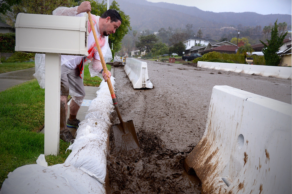 . A neighbor helps clear storm drains on Rainbow Drive in Glendora as the rainstorm starts up again Saturday afternoon, March 1, 2014. The neighborhood sits below the Colby Fire burn area. Resident Tom Tice said this was the most water and mud he\'s seen in three days of the storm. (Photo by Sarah Reingewirtz/Pasadena Star-News)