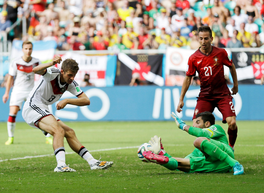 . Germany\'s Thomas Mueller (13) kicks the ball at Portugal\'s goalkeeper Rui Patricio to score his side\'s fourth goal as Portugal\'s Joao Pereira (21) watches during the group G World Cup soccer match between Germany and Portugal at the Arena Fonte Nova in Salvador, Brazil, Monday, June 16, 2014. (AP Photo/Natacha Pisarenko)