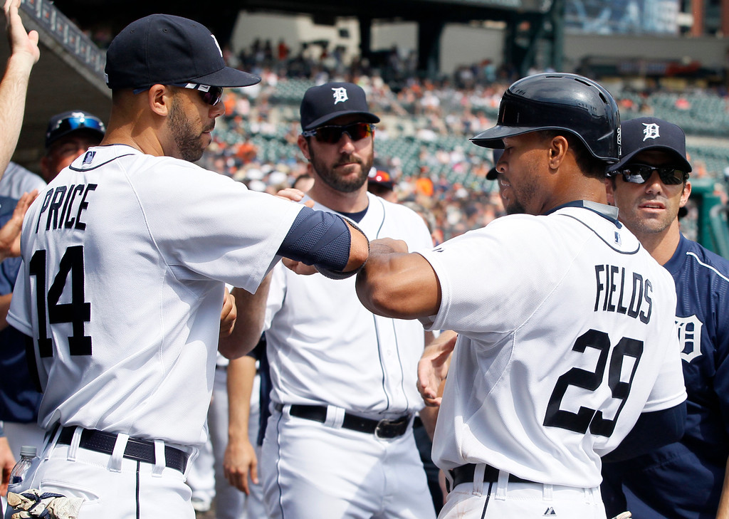. Detroit Tigers\' Daniel Fields (29) celebrates with pitcher David Price (14) after scoring against the Oakland Athletics in the ninth inning of a baseball game at Comerica Park, Thursday, June 4, 2015, in Detroit. The Athletics defeated the Tigers 7-5. (AP Photo/Duane Burleson)