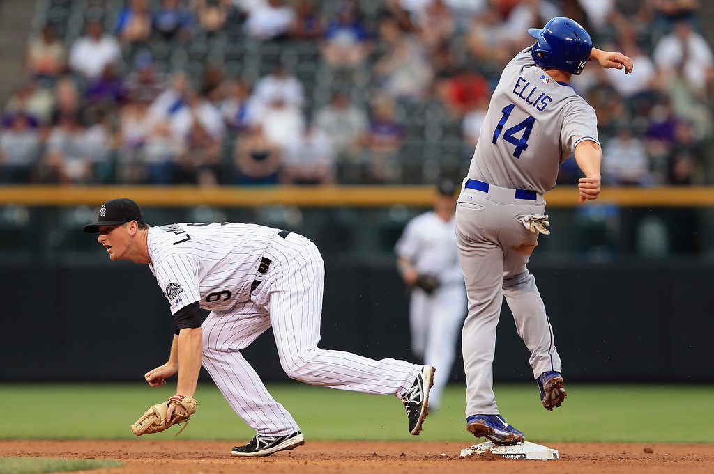 . Mark Ellis #14 of the Los Angeles Dodgers arrives safely at second base on a single by Skip Schumaker #55 of the Los Angeles Dodgers as second baseman DJ LeMahieu #9 of the Colorado Rockies covers the bag in the second inning at Coors Field on September 3, 2013 in Denver, Colorado.  (Photo by Doug Pensinger/Getty Images)