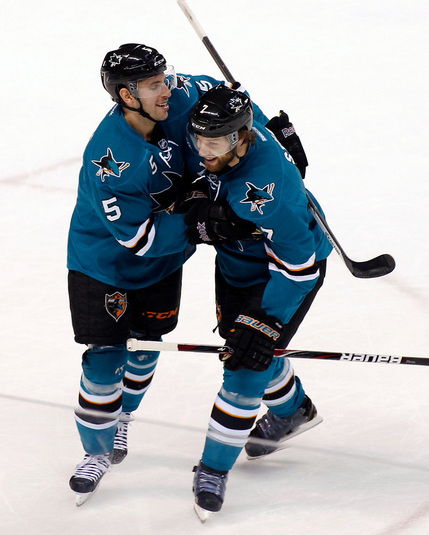 . San Jose Sharks\' Jason Demurs, left, celebrates with teammate Brad Stuart after scoring a goal against the Colorado Avalanche during the first period of an NHL hockey game, Monday, Dec. 23, 2013, in San Jose, Calif. (AP Photo/George Nikitin)