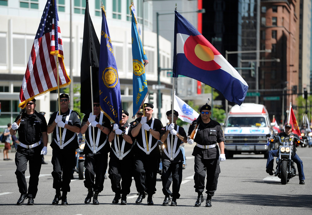 . Members of The American Legion LCW Post 1 Color Guard make their way down Broadway.(Photo By Kathryn Scott Osler/The Denver Post)
