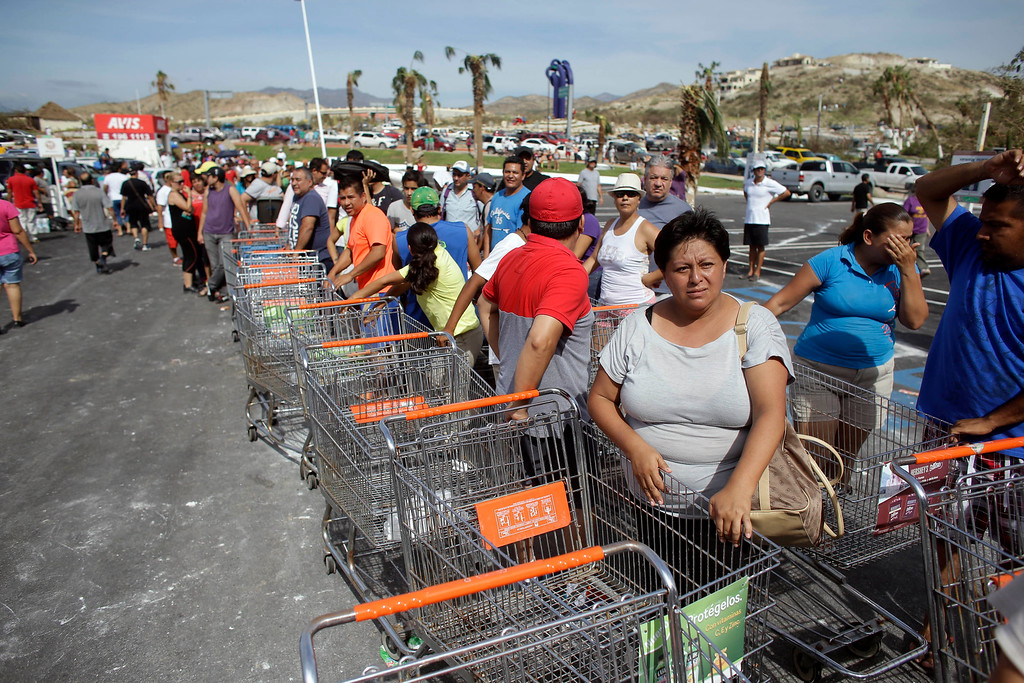 . People stand in line to get free food from a Mega Supermarket in Los Cabos, Mexico, Tuesday, Sept. 16, 2014. According to employees the supermarket donated all the food in the store and established a system by which every person had 5 minutes to get whatever they could for free. Desperate locals and tourists were in survival mode in the resort area of Los Cabos also on Wednesday, with electrical and water service still out three days after Hurricane Odile made landfall as a monster Category 3 storm. (AP Photo/Victor R. Caivano)