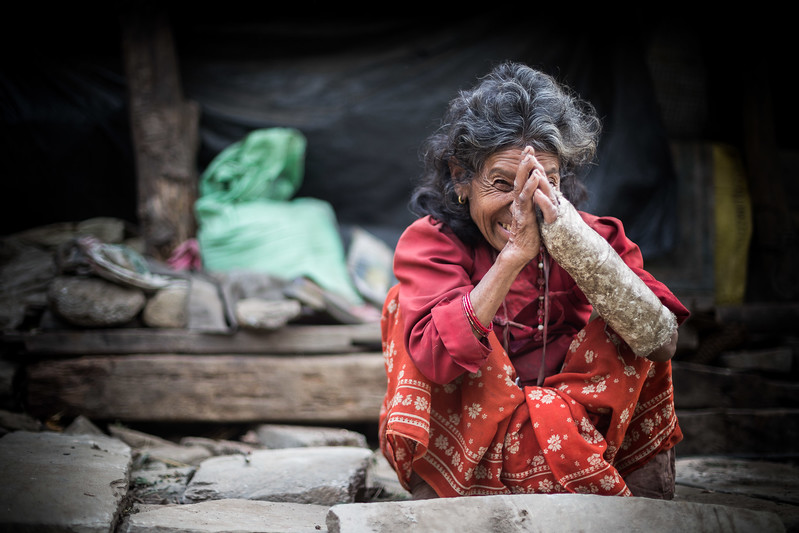 Wounded after the earthquake, a woman smiles in front of her destroyed house. Organization: CECI Nepal Sindhupalchok, Nepal. April 2015. --------- Une dame blessée suite au tremblement de terre sourit devant les restes de sa maison effondrée. Organisme: CECI Nepal Sindhupalchok, Népal. Avril 2015.