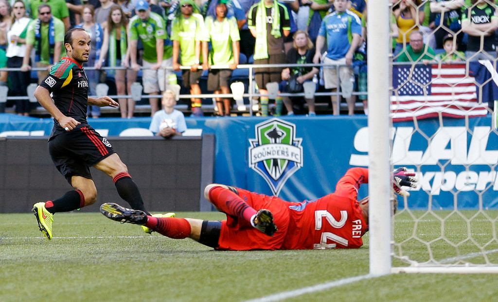 . Los Angeles Galaxy\'s Landon Donovan, left, scores a goal on Seattle Sounders goalkeeper Stefan Frei, right, in the first half of an MLS soccer match, Monday, July 28, 2014, in Seattle. (AP Photo/Ted S. Warren)