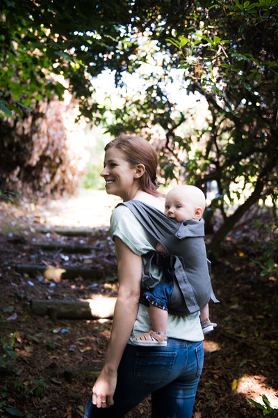 Izmi_Baby_Carrier_Mid_Grey_Lifestyle_Back_Carry_Mum_Walking_In_Woods_Side_View.jpg