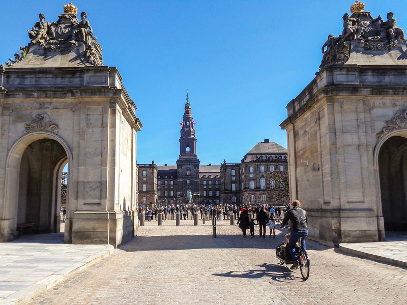 people riding bikes and walking through a large entranceway to palace with spire