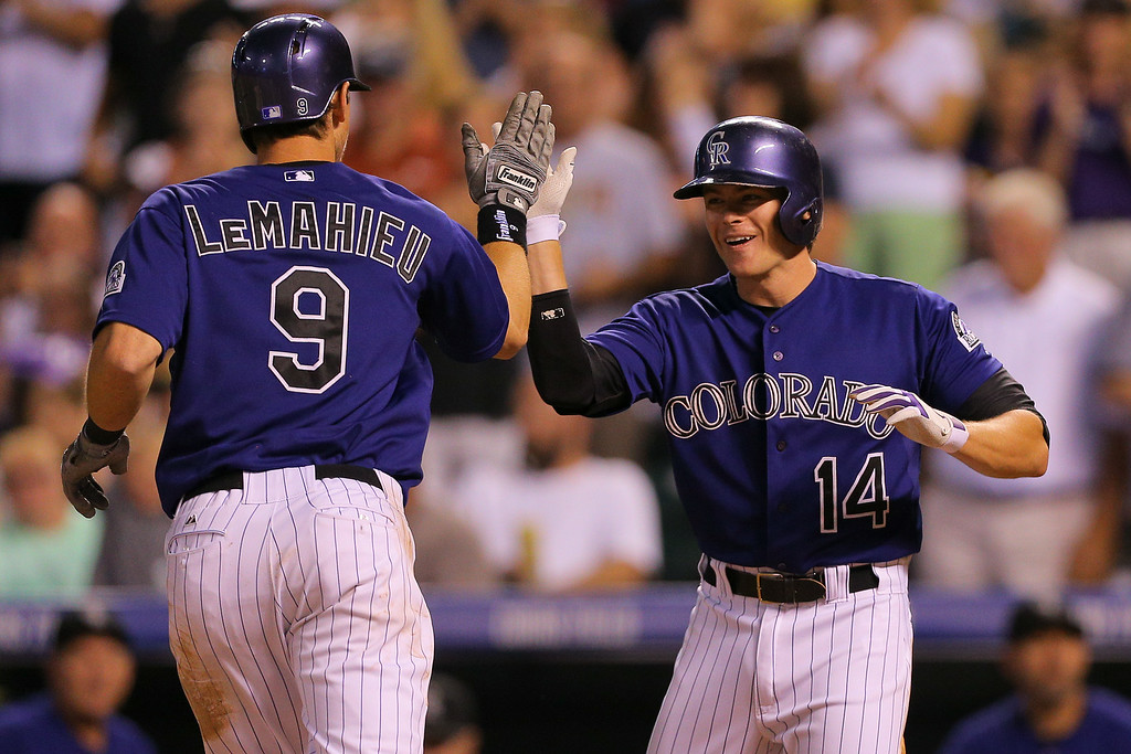 . DENVER, CO - SEPTEMBER 2:  DJ LeMahieu #9 of the Colorado Rockies is congratulated by Josh Rutledge #14 after hitting a two-run home run during the third inning against the San Francisco Giants at Coors Field on September 2, 2014 in Denver, Colorado. (Photo by Justin Edmonds/Getty Images)