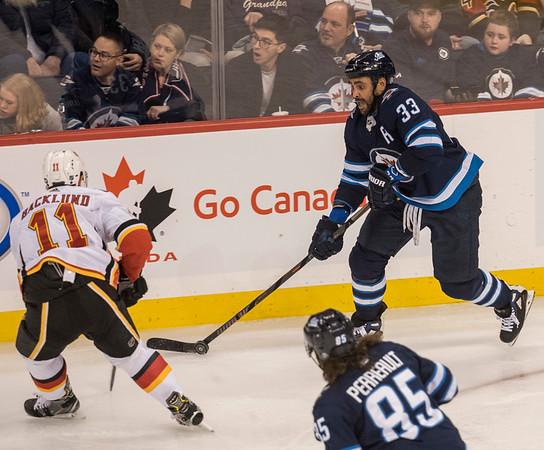 DAVID LIPNOWSKI / WINNIPEG FREE PRESS  Winnipeg Jets #33Dustin Byfuglien looks to get the puck past Calgary Flames #11 Mikael Backlund Thursday December 27, 2018 at Bell MTS Place.