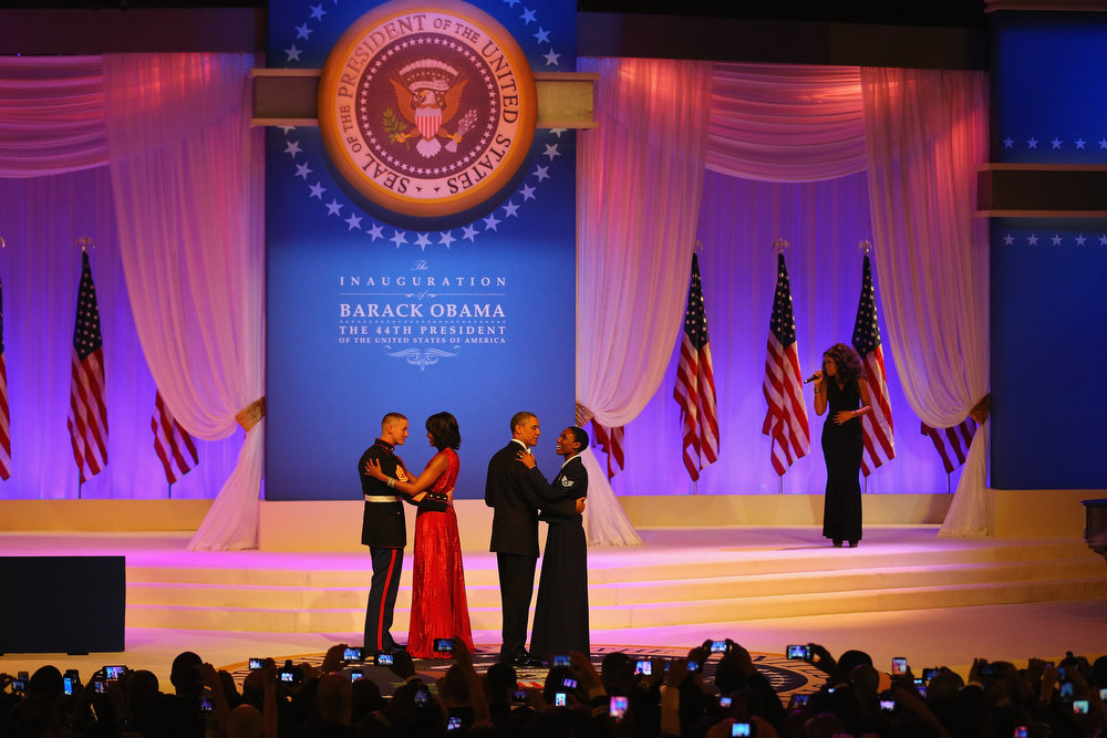 Description of . U.S. President Barack Obama dances with Air Force Staff Sergeant Bria Nelson as first lady Michelle Obama dances with Marine Gunnery Sergeant Timothy Easterling as sincer Jennifer Hudson performs during the Commander-In-Chief's Inaugural Ball January 21, 2013 in Washington, DC. Obama was sworn in today for his second term in a public ceremonial swearing in..  (Photo by Joe Raedle/Getty Images)