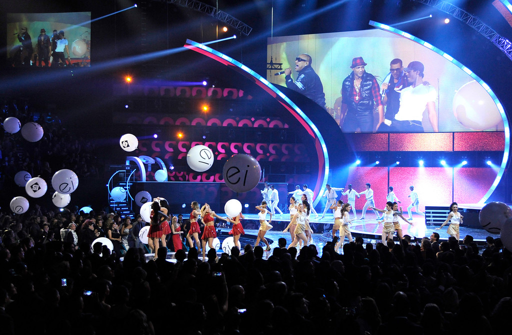 . Alexander Delgado, left, and Randy Malcom, second right, of the musical group Gente de Zona, Julio Iglesias, right, and Descemer Bueno appear on screen performing via satellite at the 15th annual Latin Grammy Awards at the MGM Grand Garden Arena on Thursday, Nov. 20, 2014, in Las Vegas. (Photo by Chris Pizzello/Invision/AP)