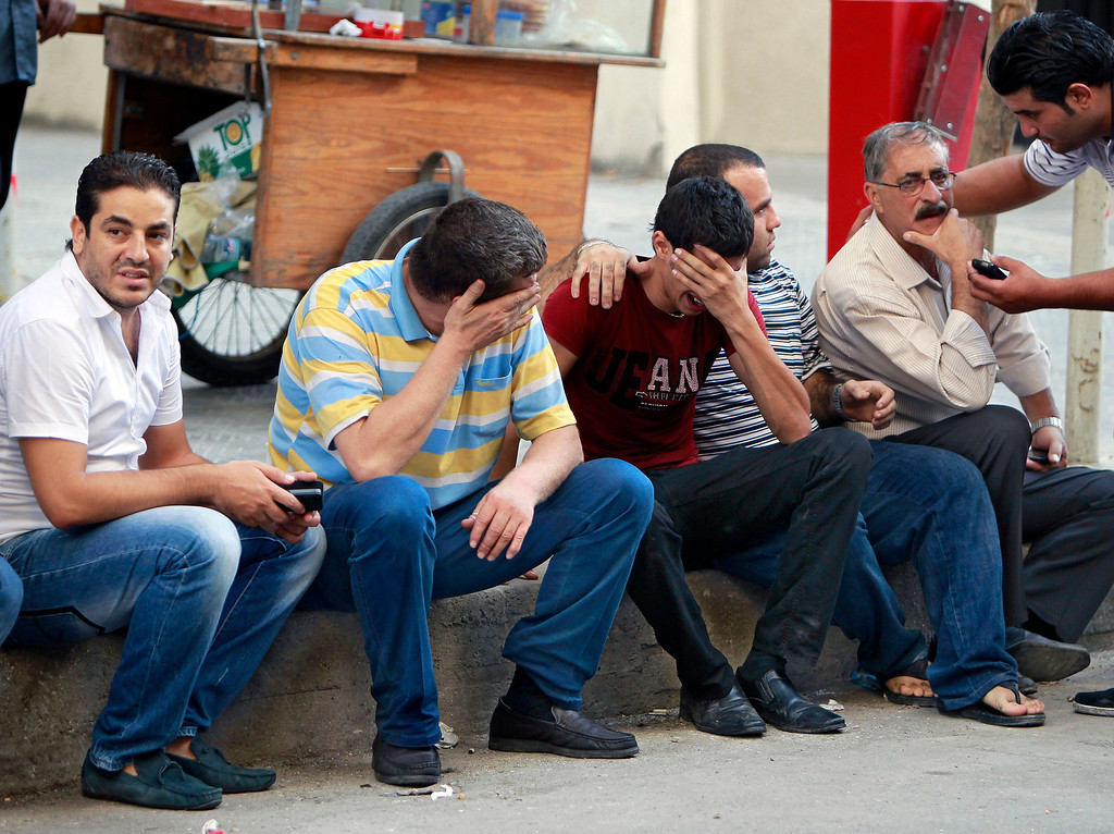. Lebanese men weep outside the Islamic Hospital after hearing that a relative was killed in a car bomb attack, in the northern city of Tripoli, Lebanon, Friday, Aug. 23, 2013.  (AP Photo/Bilal Hussein)