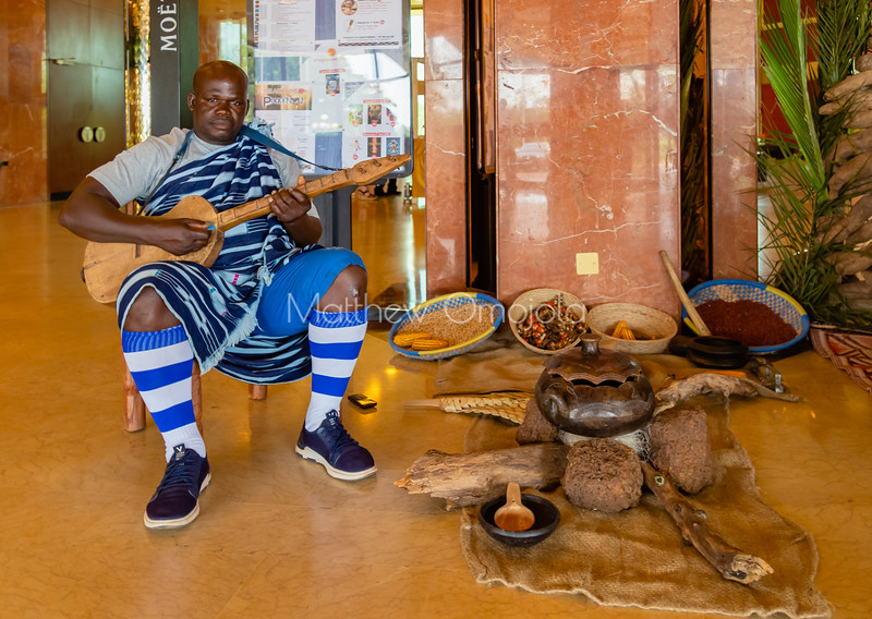 Ivorian musician playing local instrument at president hotel yamoussoukro Ivory Coast Cote d'Ivoire wearing african attire promoting culture.