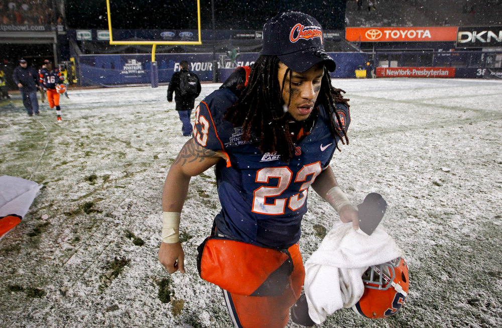 Description of . Bowl MVP Prince-Tyson Gulley #23 of the Syracuse Orange runs off the field after a win over the West Virginia Mountaineers in the New Era Pinstripe Bowl at Yankee Stadium on December 29, 2012 in the Bronx borough of New York City.  (Photo by Jeff Zelevansky/Getty Images)