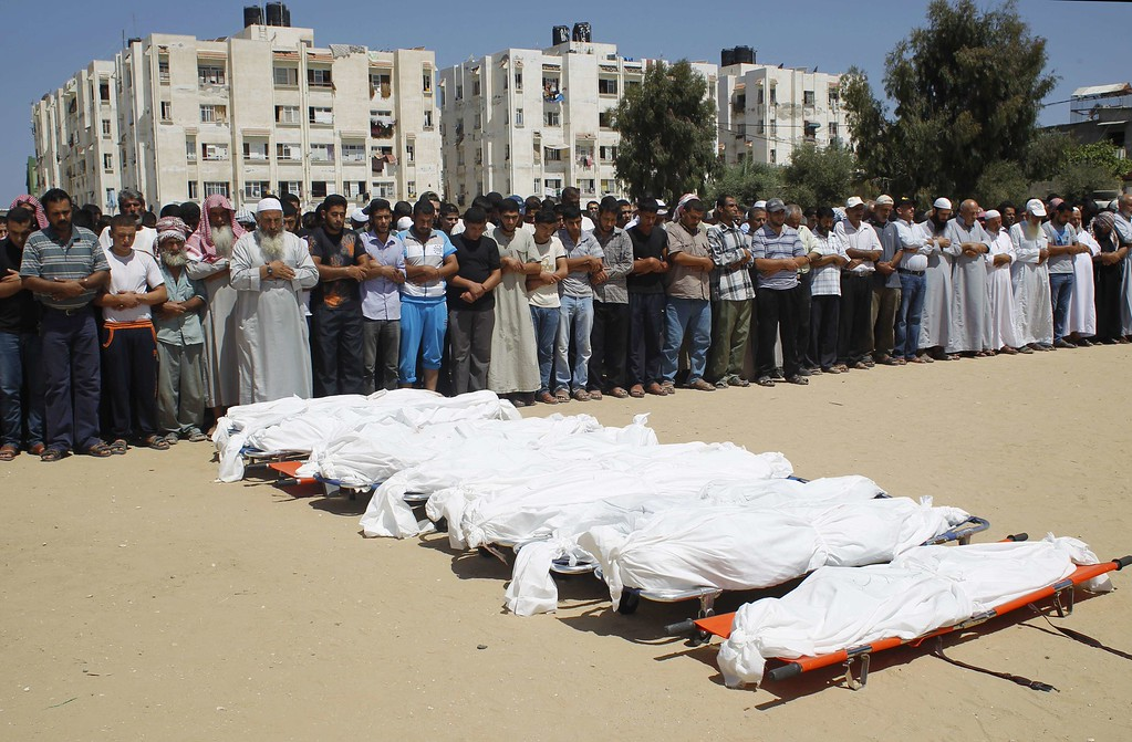 ". Palestinian mourners pray in front of the bodies of ten members of the al-Astal family, that were killed in an Israeli air strike on their homes, during their funeral in Khan Yunis in the southern Gaza Strip on July 30, 2014. Israeli bombardments early on July 30 killed ""dozens\"" Palestinians in Gaza, including at least 16 at a UN school, medics said, on day 23 of the Israel-Hamas conflict. AFP PHOTO/ SAID  KHATIB/AFP/Getty Images"