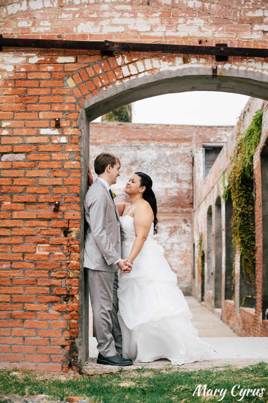 Bride & Groom posing in an arch after their ceremony at the McKinney Cotton Mill | Photo by Mary Cyrus Photography - Weddings & Portraits in Dallas & Beyond