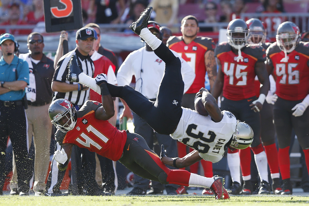 . TAMPA, FL - DECEMBER 28: Travaris Cadet #39 of the New Orleans Saints gets tripped up along the sideline by C.J. Wilson #41 of the Tampa Bay Buccaneers in the second half of the game at Raymond James Stadium on December 28, 2014 in Tampa, Florida. The Saints defeated the Bucs 23-20. (Photo by Joe Robbins/Getty Images)