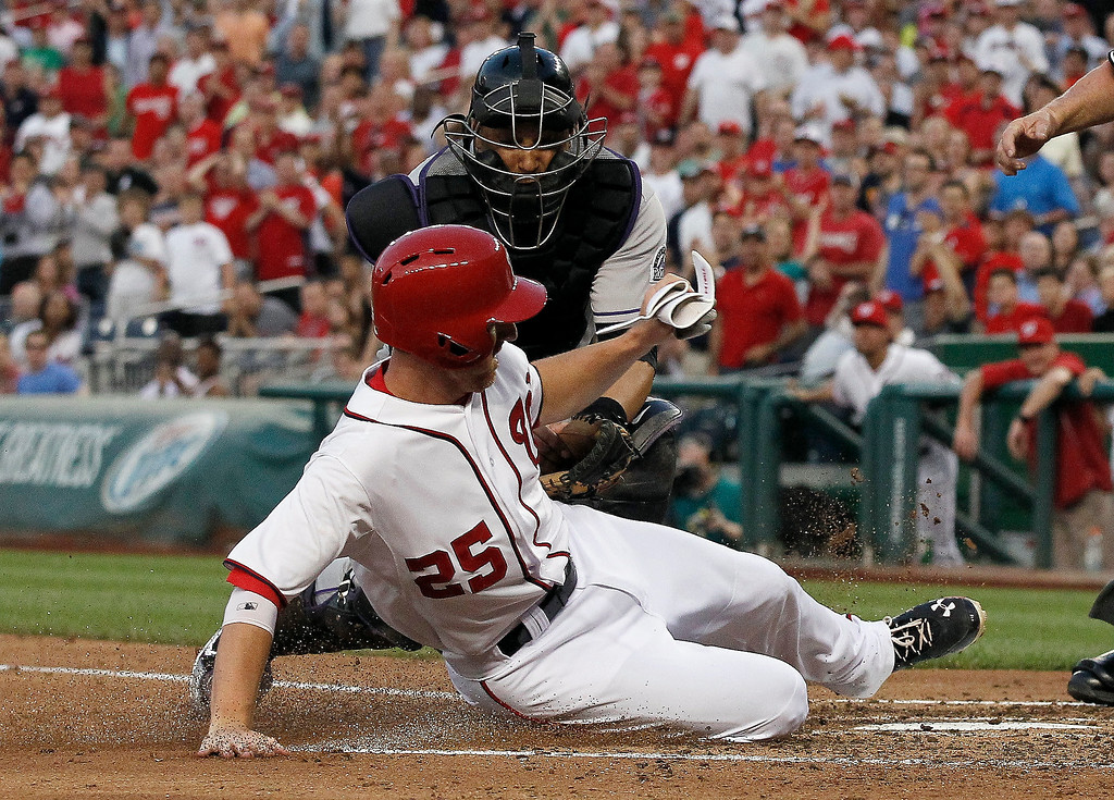 . Washington Nationals\' Adam LaRoche (25) slides safely into home plate as Colorado Rockies catcher Yorvit Torrealba (8) tries to put the tag on him during the fourth inning of a baseball game at Nationals Park, Thursday, June 20, 2013, in Washington. (AP Photo/Alex Brandon)