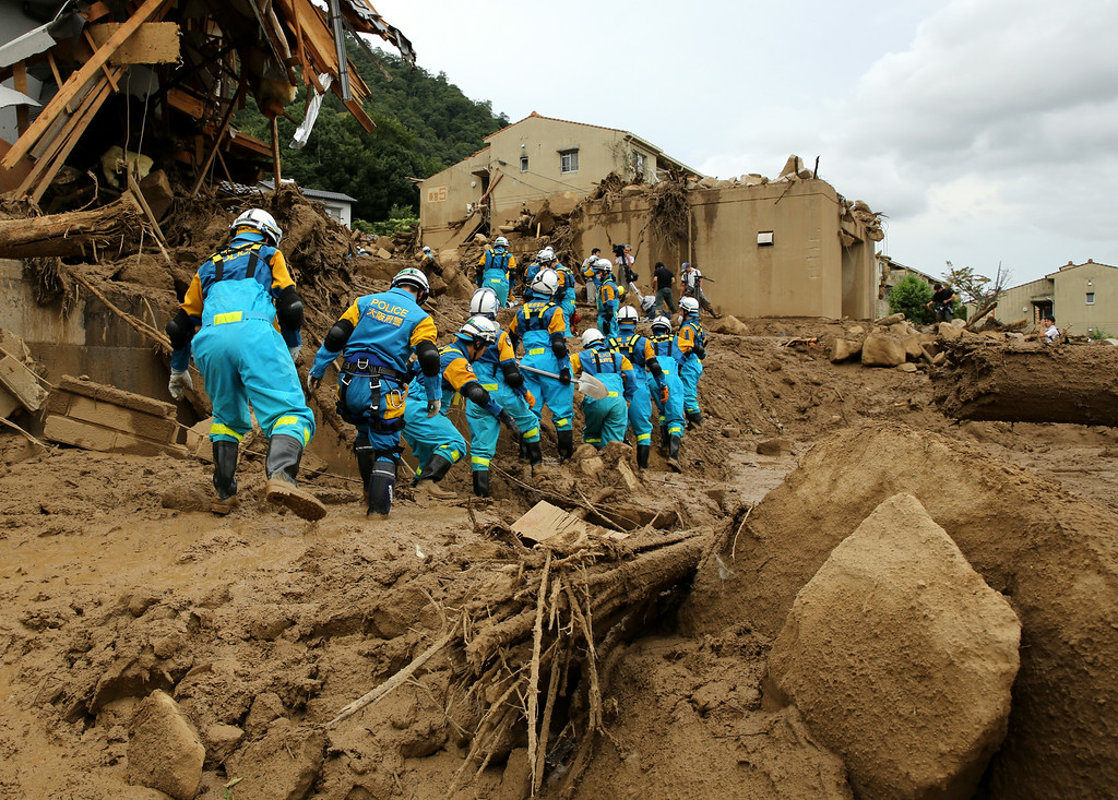 . Members of Police walk to doing rescue work in an area damaged by a landslide caused by torrential rain at the site of a landslide in a residential area on August 20, 2014 in Hiroshima, Japan.   (Photo by Buddhika Weerasinghe/Getty Images)