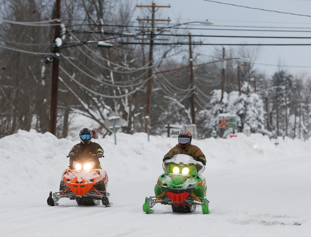 . Volunteer firefighters ride snowmobiles alone Clinton Street on Thursday, Nov. 20, 2014, in West Seneca, N.Y. A new blast of lake-effect snow pounded Buffalo for a third day piling more misery on a city already buried by an epic, deadly snowfall that could leave some areas with nearly 8 feet of snow on the ground when it\'s all done. (AP Photo/Mike Groll)