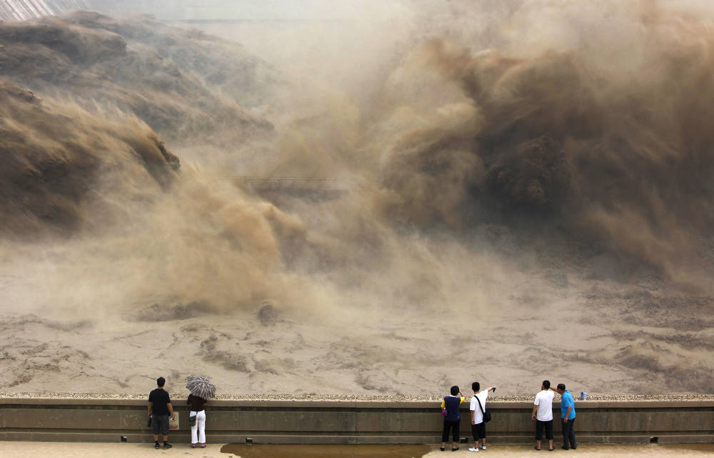 . This picture taken on July 6, 2012 shows visitors gathering to giant gushes of water released from the Xiaolangdi dam to clear up the sediment-laden Yellow river and to prevent localized flooding, in Jiyuan, central China\'s Henan province. China is hit by big downpours every summer often causing fatalities as seen in 2010, which saw the nation\'s worst flooding in a decade leaving more than 4,300 people dead or missing.      AFP PHOTOSTR/AFP/Getty Images