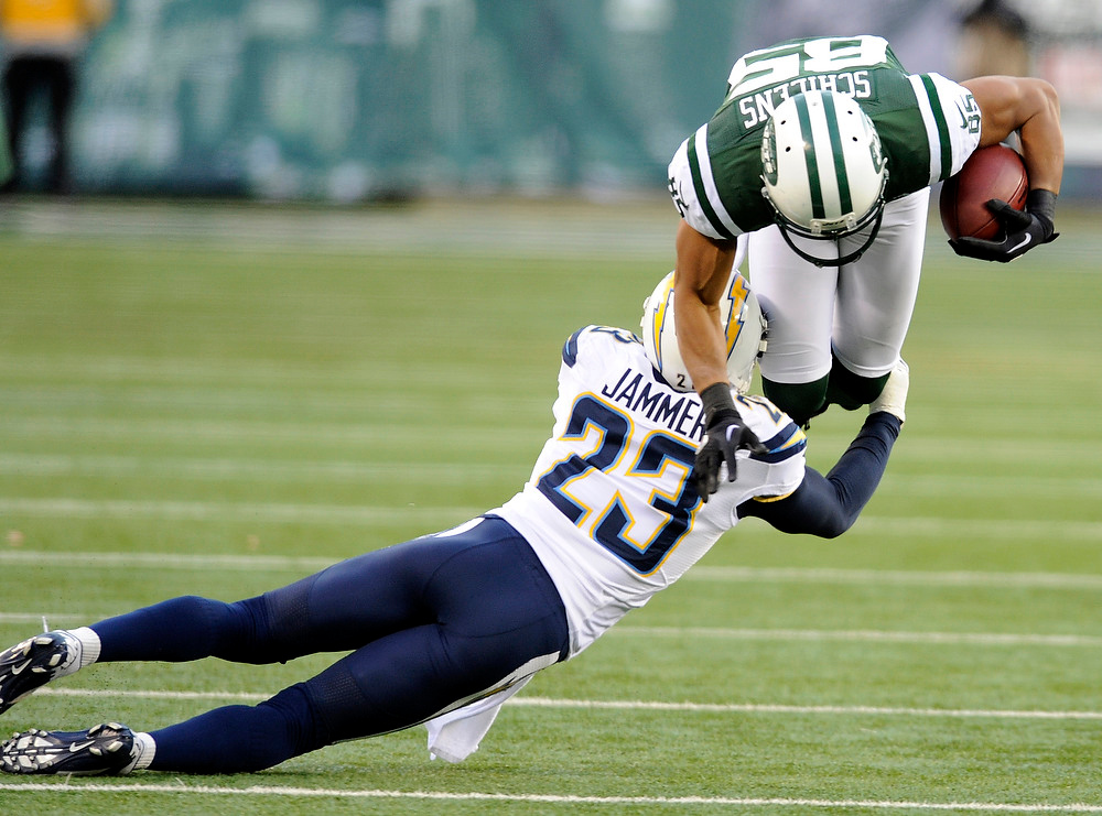 Description of . New York Jets wide receiver Chaz Schilens, right, goes airborne as San Diego Chargers cornerback Quentin Jammer (23) makes the tackle during the second half of an NFL football game on Sunday, Dec. 23, 2012, in East Rutherford, N.J. (AP Photo/Bill Kostroun)
