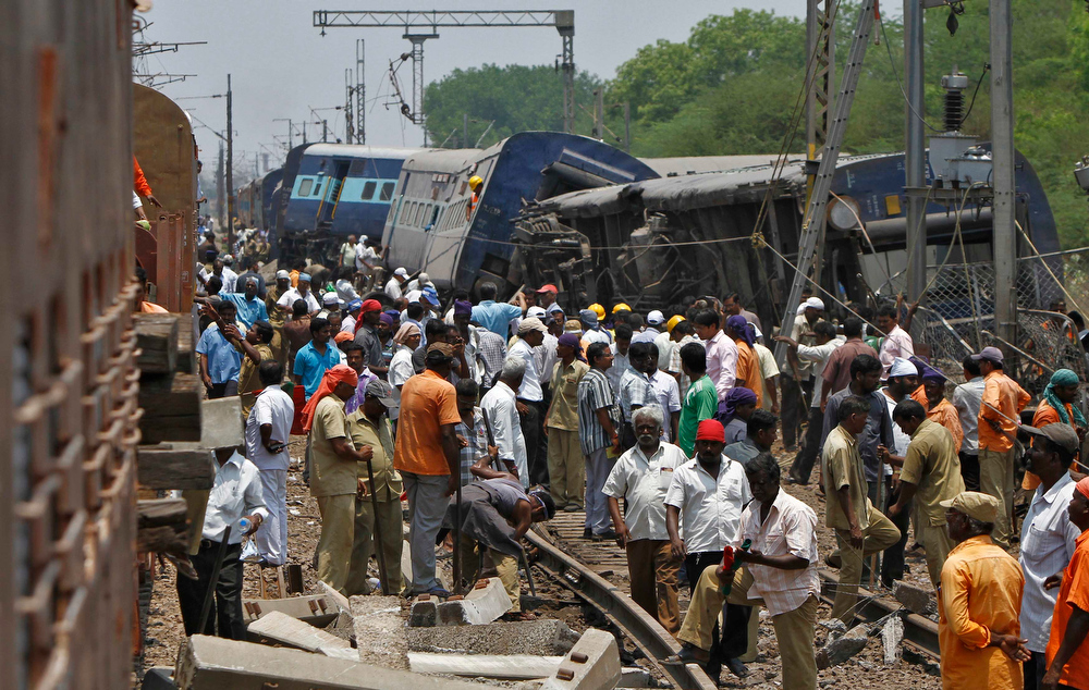 . Rescue workers and onlookers stand next to the derailed coaches at the site of a train accident near Arakkonam in the southern Indian state of Tamil Nadu April 10, 2013. One person was killed and dozens were injured after a passenger train derailed in Tamil Nadu, local media reported on Wednesday. REUTERS/Babu