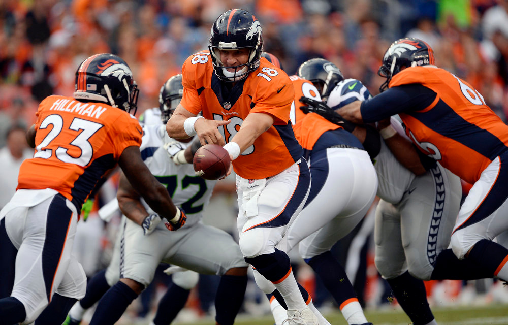 . Quarterback Peyton Manning (18) of the Denver Broncos hands off to running back Ronnie Hillman (23) of the Denver Broncos during the first quarter.  The Denver Broncos vs the Seattle Seahawks At Sports Authority Field at Mile High. (Photo by AAron Ontiveroz/The Denver Post)