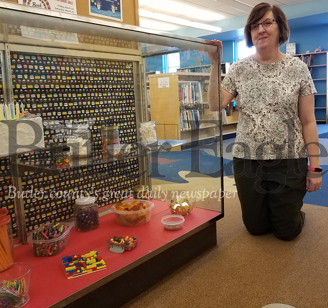 Butler Library Executive Director Linda Hinderliter shows off the display case in the children's section of the library that holds collections of 125 things gathered in honor of the library's 125th anniversary. PHOTO BY ERIC FREEHLING