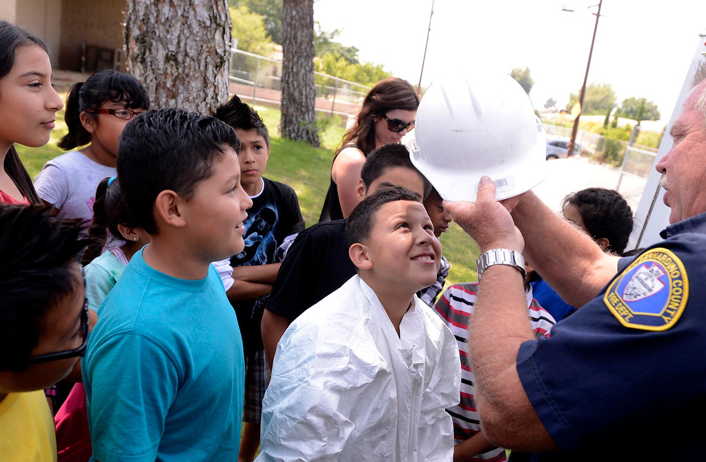 . Brian Otter of San Bernardino County Fire/ Hazardous Material, right,  outfits fourth grader Donovan Barajas with a helmet during the final day of the 19th Annual Career Awareness Week at Lankershim Elementary School in Highland June 6, 2013.  GABRIEL LUIS ACOSTA/STAFF PHOTOGRAPHER.