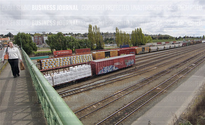 A pedestrian crosses the Dravus Street overpass over trains queued up in the Balmer Yard of the Interbay neighborhood of Seattle, Washington