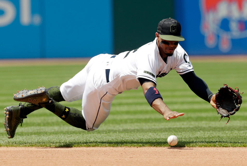 . Cleveland Indians\' Francisco Lindor dives for a ball hit by Houston Astros\' Jose Altuve in the fourth inning of a baseball game Sunday, May 27, 2018, in Cleveland. Altuve was safe at first base on the play. (AP Photo/Tony Dejak)