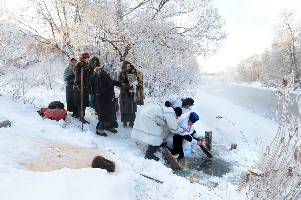 . Two believers support a Russian Orthodox priest blessing water in a river on the eve of Russian Orthodox Epiphany in the village of Fedorovskoye, some 100 km (63 miles) southeast of Moscow, Saturday, Jan. 18, 2014. Water that is blessed by a cleric on Epiphany is considered holy and pure and believed to have special powers of protection and healing. Thousands of Russian Orthodox Church followers will plunge into icy rivers and ponds across the country to mark Epiphany, cleansing themselves with water deemed holy for the day.  (AP Photo/Vladimir Khodakov)